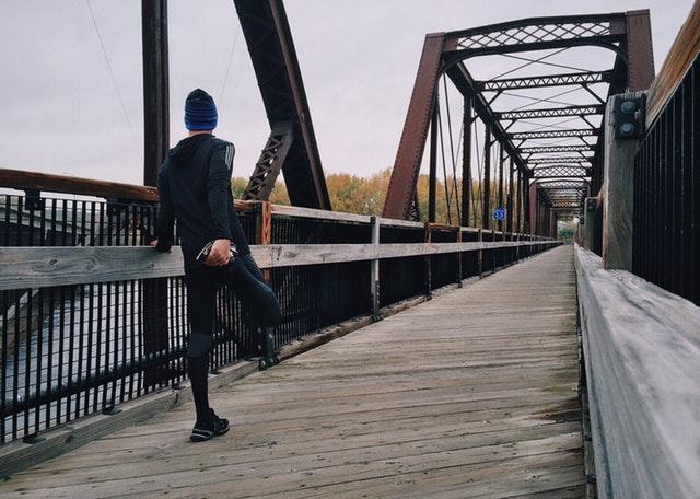 Muž, ve sportovním, rozcvičující se na mostě