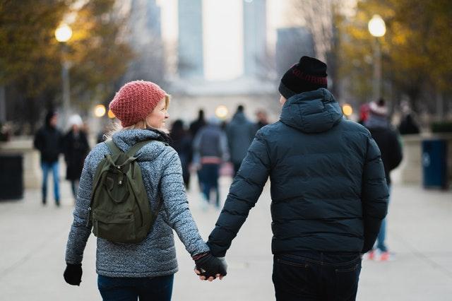 Žena s batohem na zádech držící za ruku muže, jdoucí městem