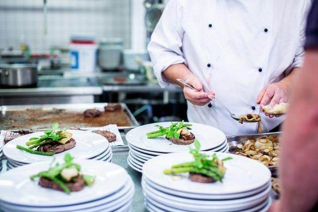 Detail hotelové kuchyně-kuchař dávající jídlo na talíře