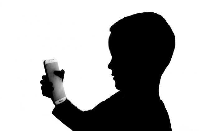 stín dítěte hledící na chytrý telefon na bílém pozadí